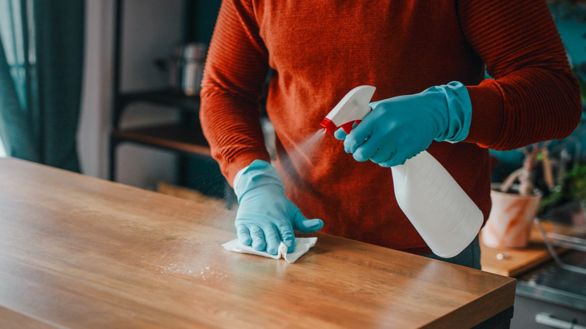 A man sprays and disinfects a countertop with a spray bottle that contains a disinfectant solution.