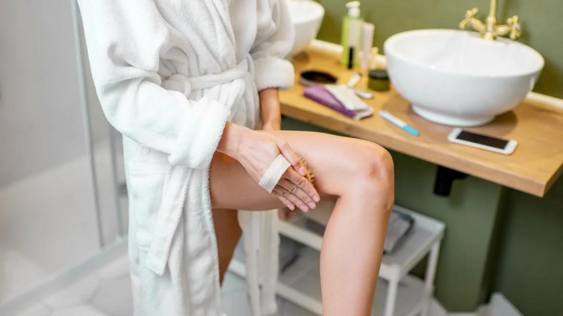 Uma mulher com um roupão de banho está no banheiro enquanto usa uma escova seca na coxa direita.