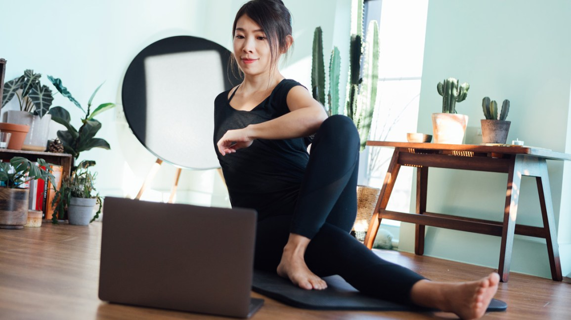 A person seated on the floor of their home stretches during yoga