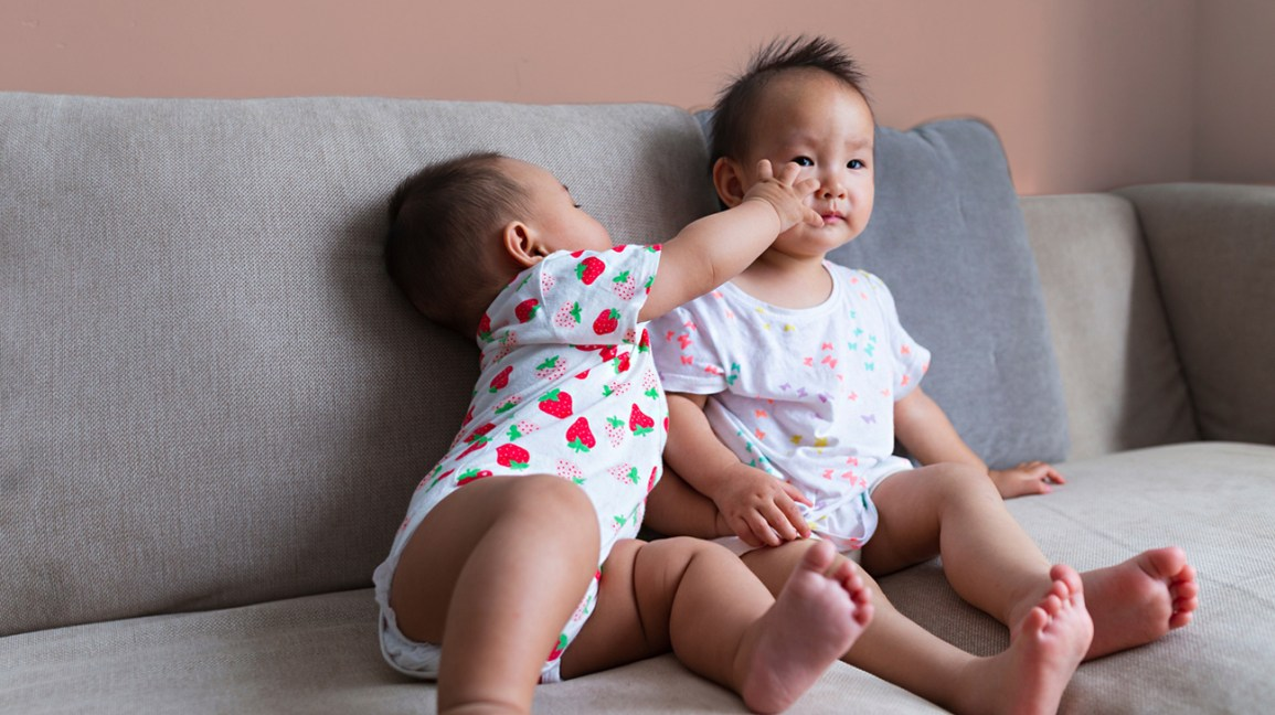 Baby reaching across body to touch sibling
