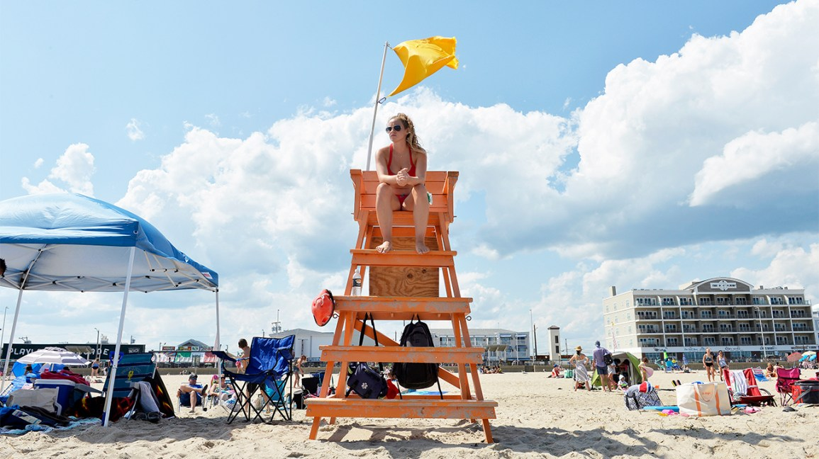 A lifeguard sits on a raised chair above the sand, looking out at the crowded beach