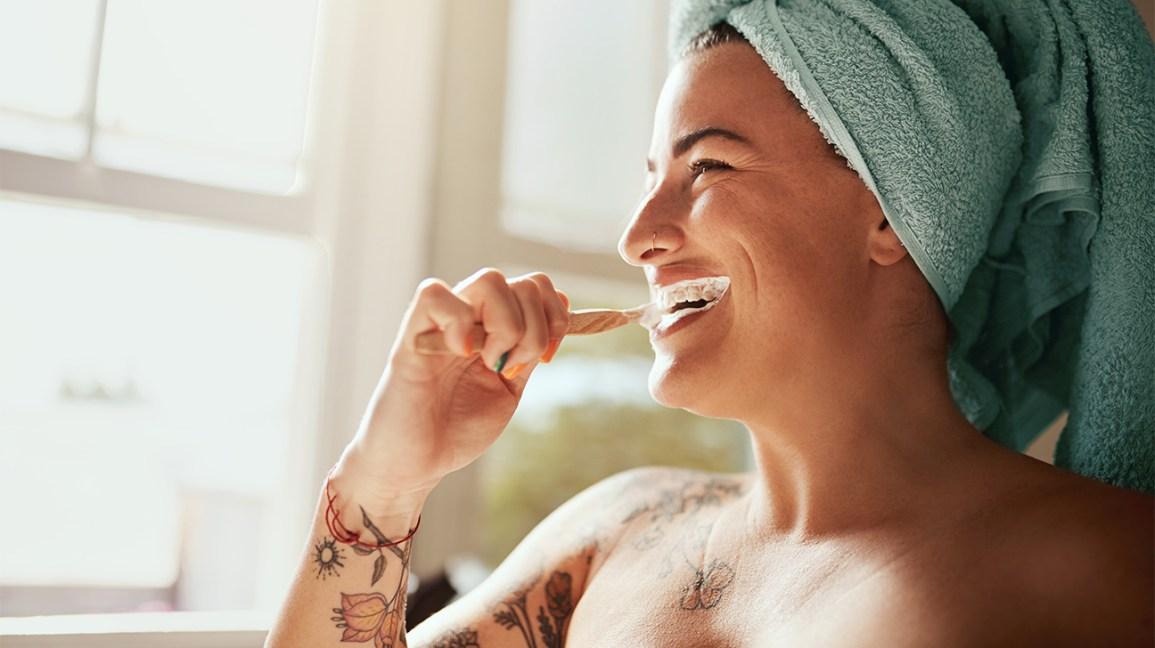 Una donna in piedi in un bagno, con un asciugamano avvolto intorno alla testa, si pulisce i denti con uno spazzolino da denti.