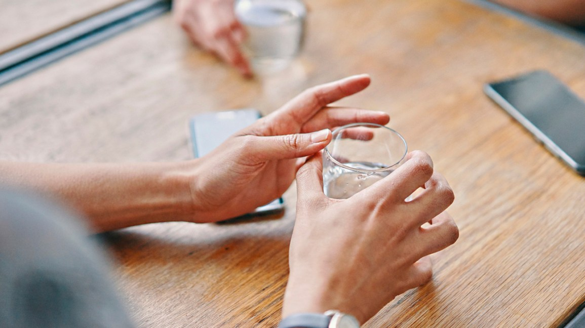 A person sits at a table with a glass of water in their hands.