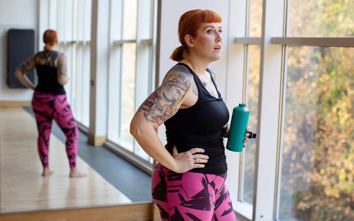 A woman in workout gear holds a water bottle while looking out of a window.