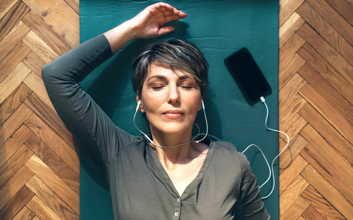 A woman lies on the ground with her eyes closed, wearing earbuds, while listening to guided imagery audio.