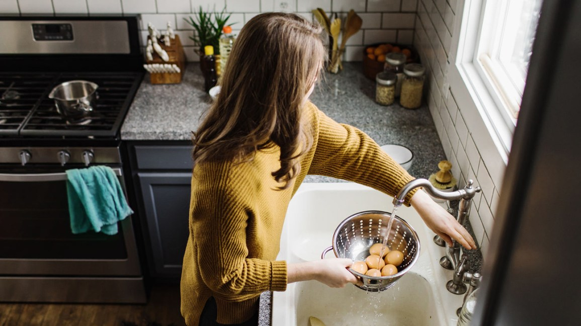 a woman rinsing hard-boiled eggs