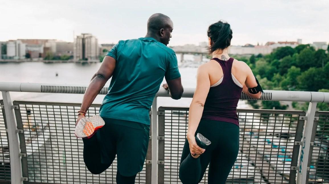 Um homem e uma mulher estão próximos a uma grade enquanto alongam seus quadríceps.