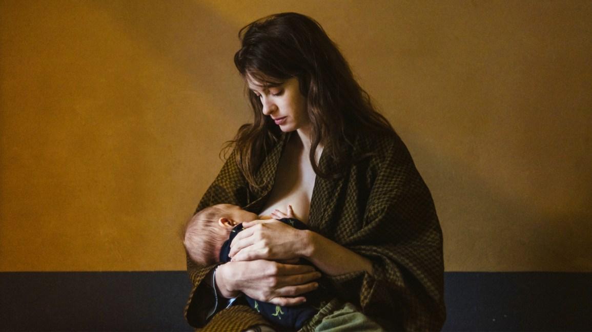 Mulher amamentando bebê em quarto escuro
