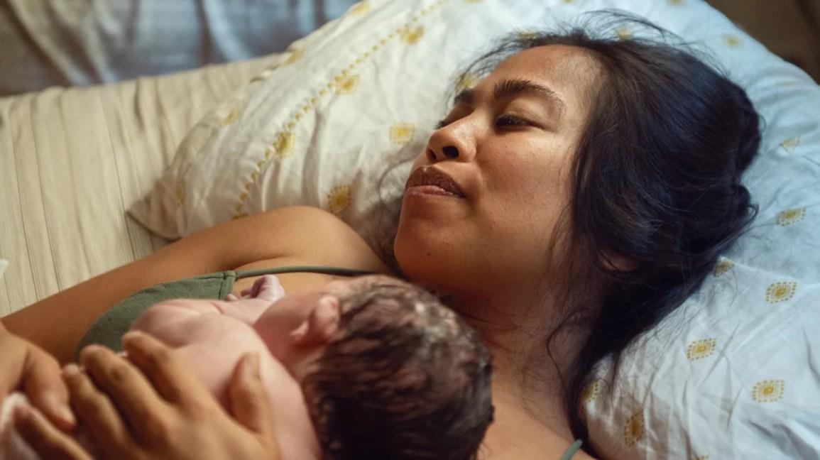 mãe embala o recém-nascido após o nascimento