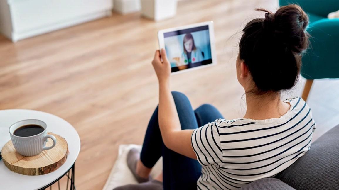 Uma mulher se senta no chão de sua sala de estar, enquanto consulta um terapeuta online, por meio de um iPad.