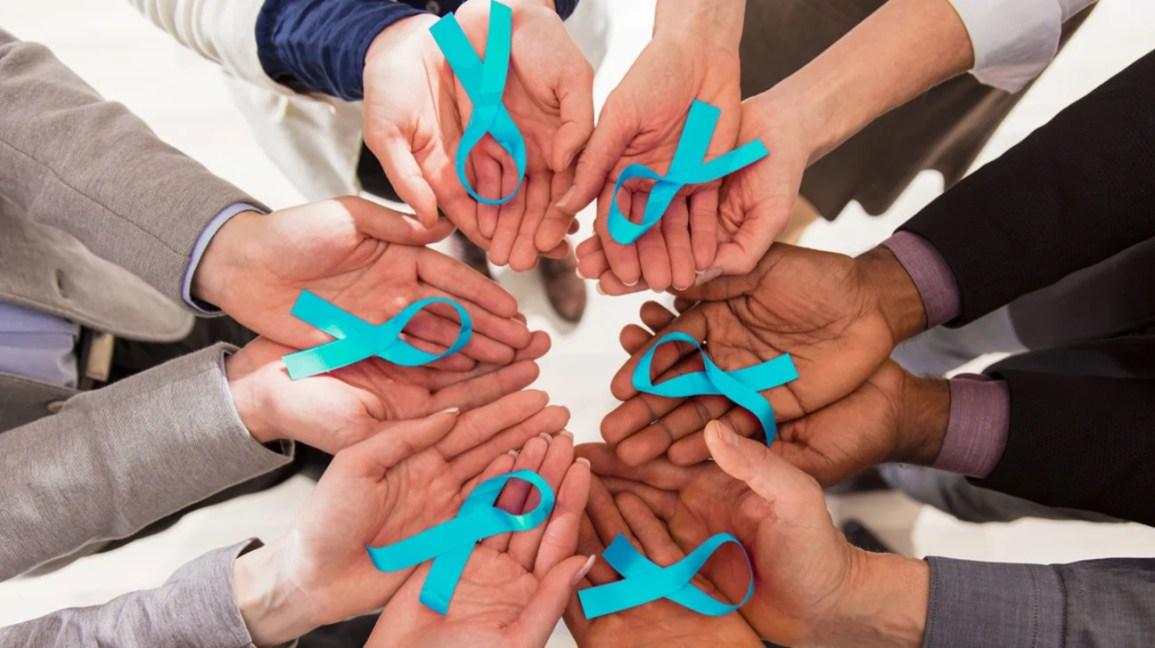 círculo de mãos segurando fitas de conscientização do câncer de ovário azul-petróleo