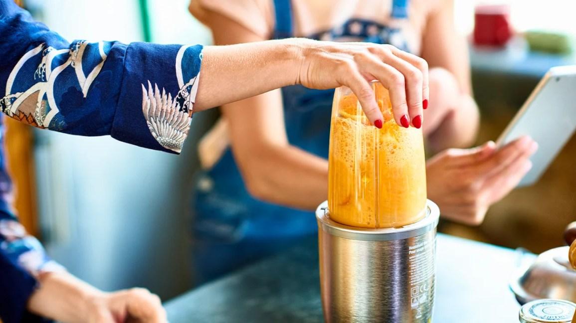 orange smoothie in a hand blender