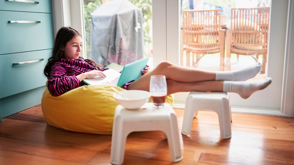 adolescente em seu laptop com lanche por perto