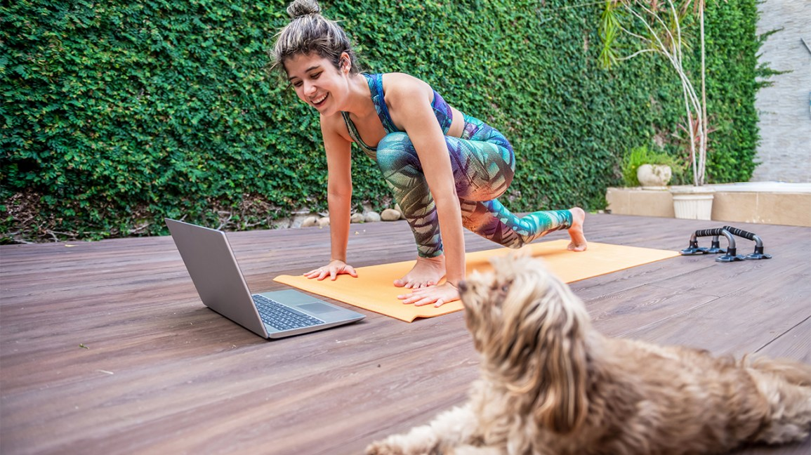 woman doing yoga outside in front of laptop