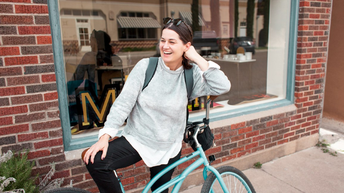 woman leaning on bike smiling