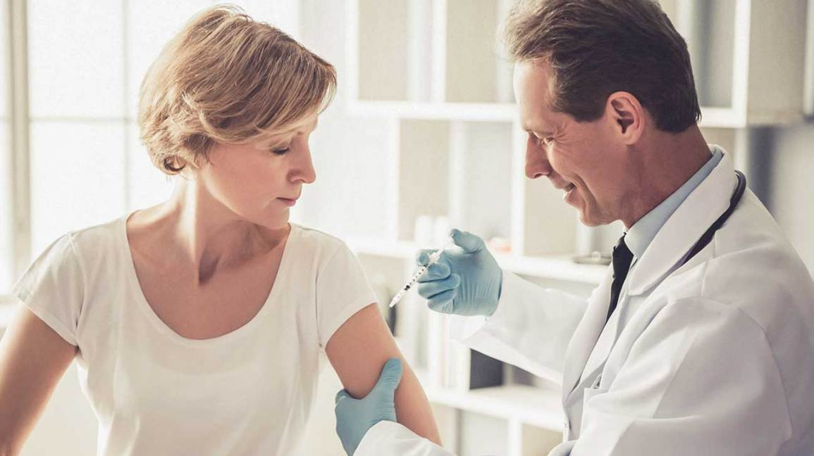 male doctor giving a woman an injection in her upper left arm