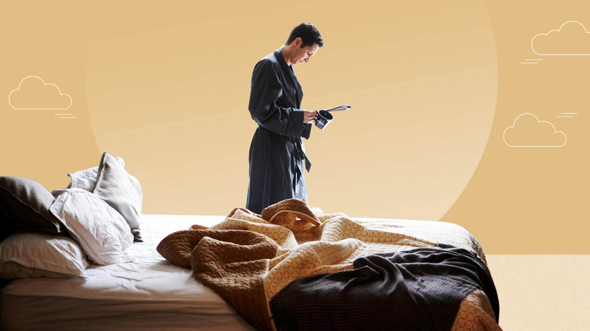 man standing near king size mattress and reading a newspaper