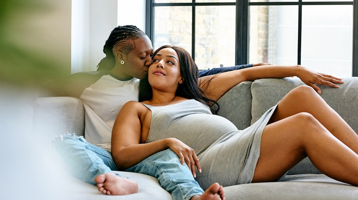 Pregnant person and partner lounging on couch
