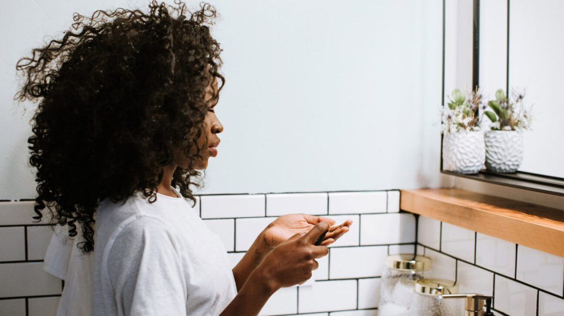 A woman stands in front of a bathroom mirror, getting ready to start her skincare routine.