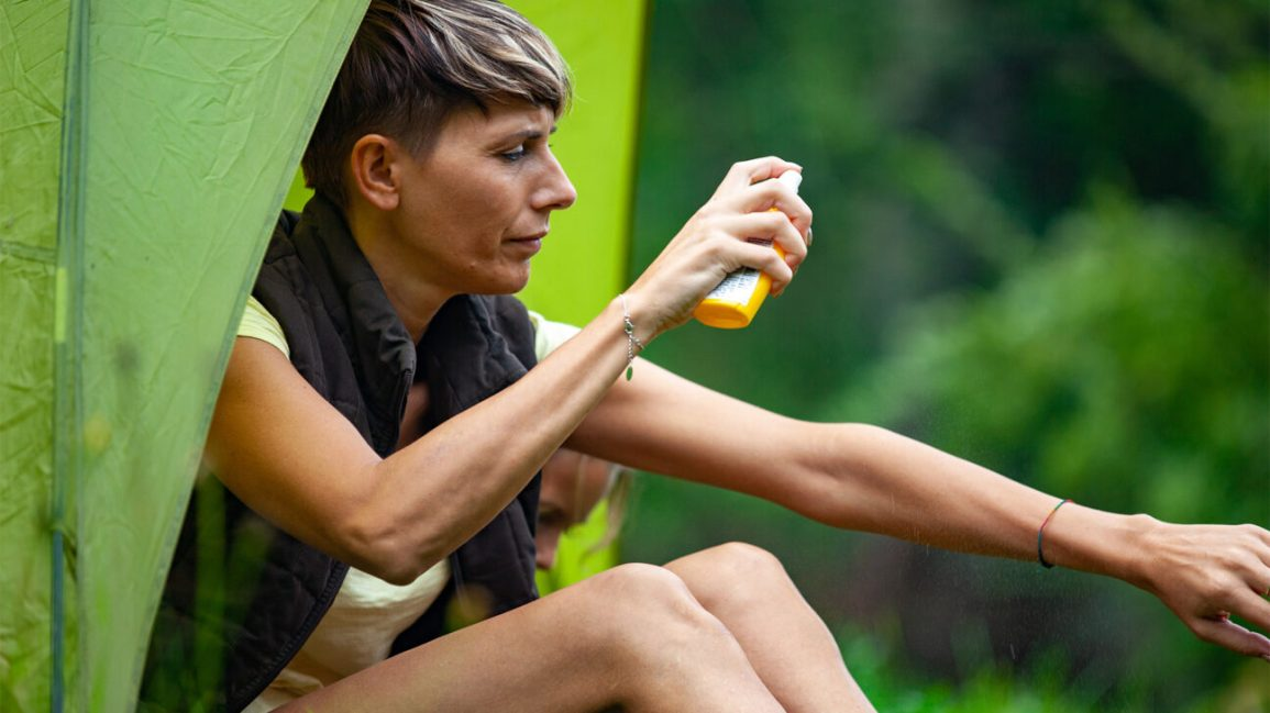 A woman sits outdoors and sprays mosquito repellent on her arms.