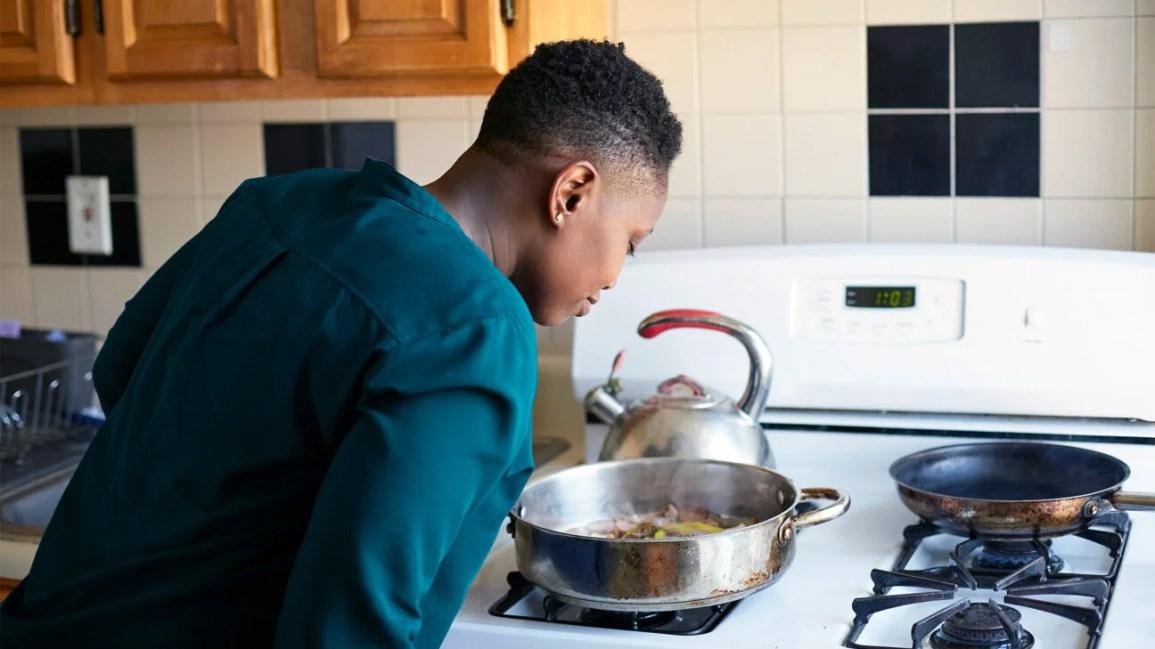 Una donna si china su una pentola sul fornello per annusare il cibo che sta cuocendo.