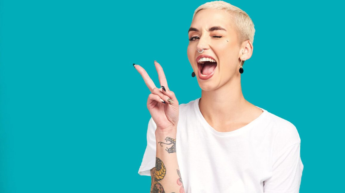 woman with tattoos and piercings giving peace sign and winking