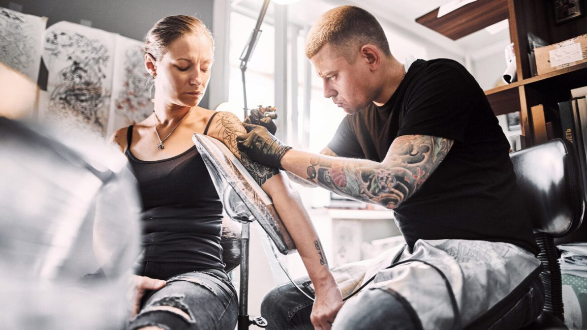 neosporin on tattoo, woman getting a tattoo