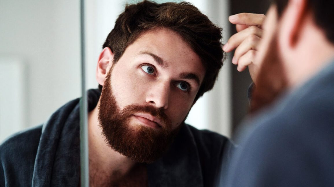 male looks in the mirror for hair loss