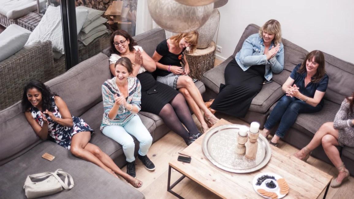 Uma foto aérea de um grupo de mulheres sentadas em sofás em uma festa em casa.