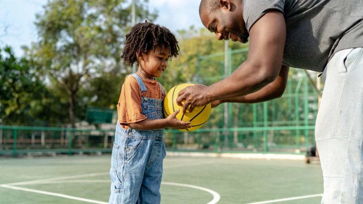 felice genitore e figlio giocano a basket insieme