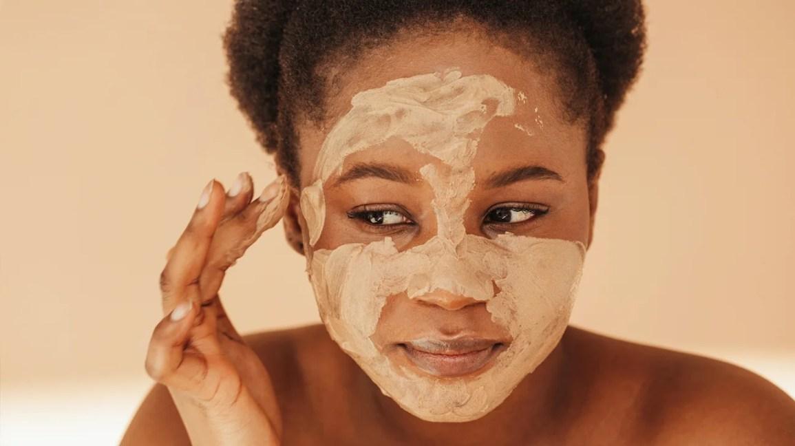 immagine ravvicinata di una persona con i capelli castani tirati via dal viso da una fascia che applica sulla pelle una maschera di fango color crema