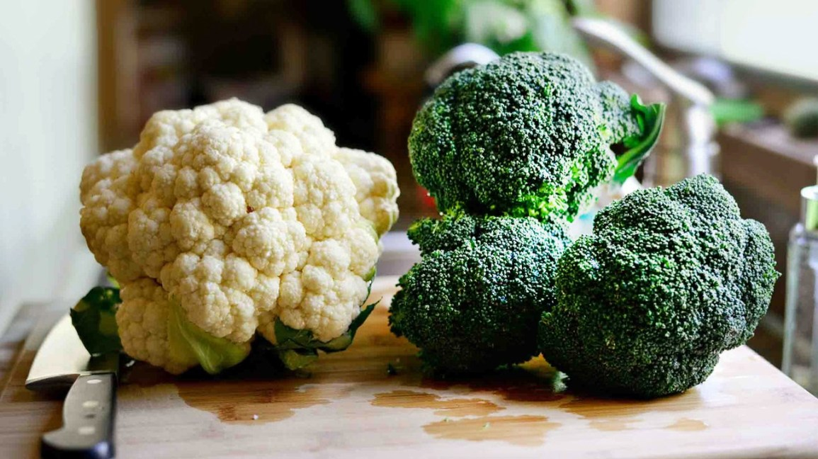 raw heads of cauliflower and broccoli on a cutting board