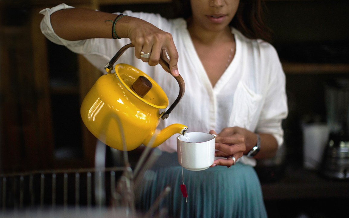 woman pouring hot water into a tea mug