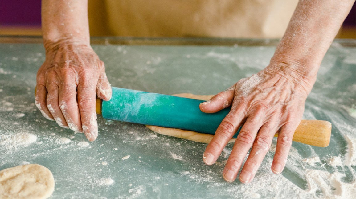 close-up of the hands of a person rolling dough with a turquoise rolling pin