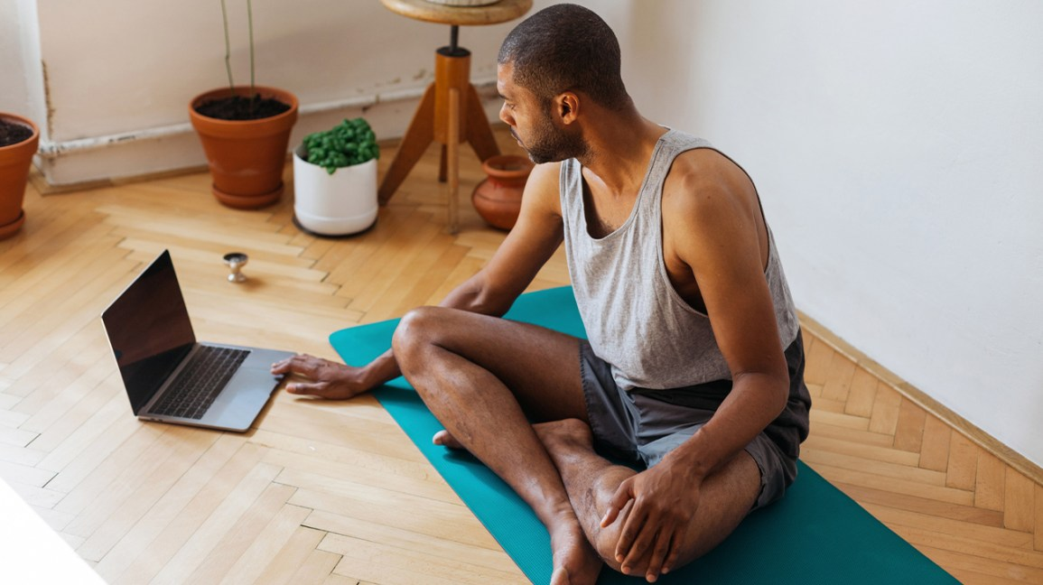 man sitting on yoga mat