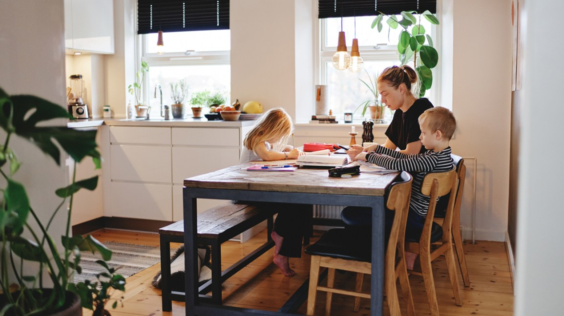 parent and children homeschooling at dinner table