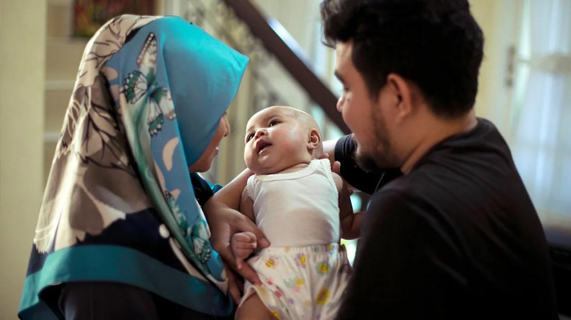 genitori che tengono il neonato a casa