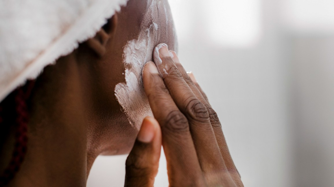 A woman applies a skin care product to her face with her fingers.