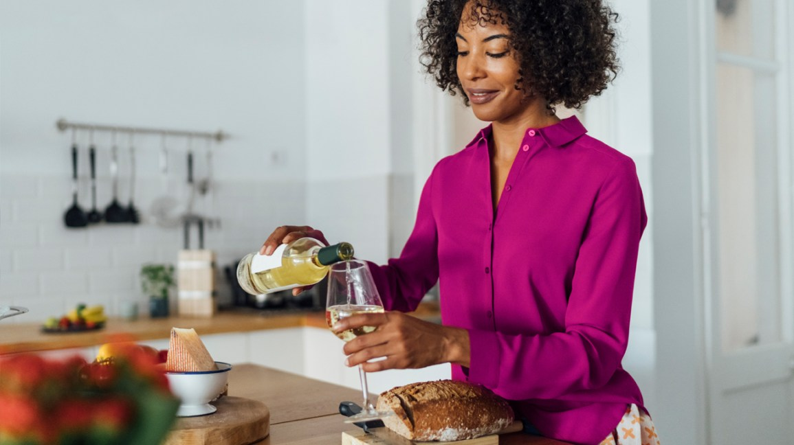 A woman stands in her kitchen and pours a glass of wine.