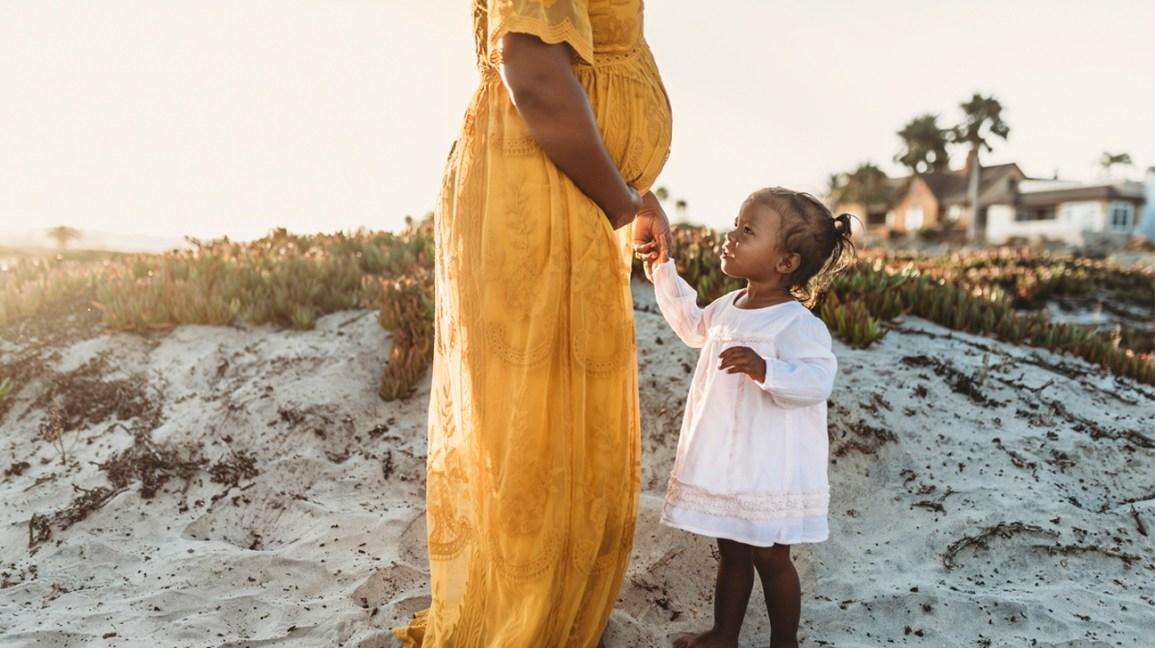Orang hamil di pantai dengan anak perempuannya