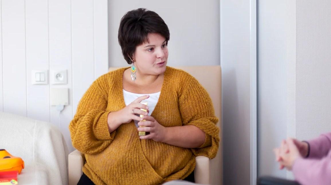 terapeuta sentada em uma cadeira rosa claro