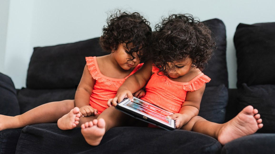 identical twin toddlers play with tablet