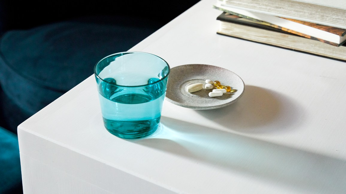 Pills on table next to glass of water