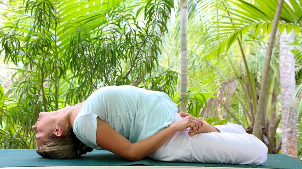 Uma mulher está deitada em um tapete, fazendo uma pose de ioga para ajudar a curar o chakra da garganta.