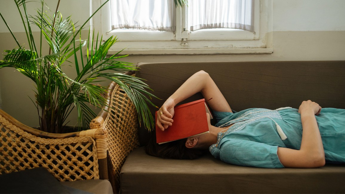 A woman lies on a couch, with a book over her face, while taking a catnap.