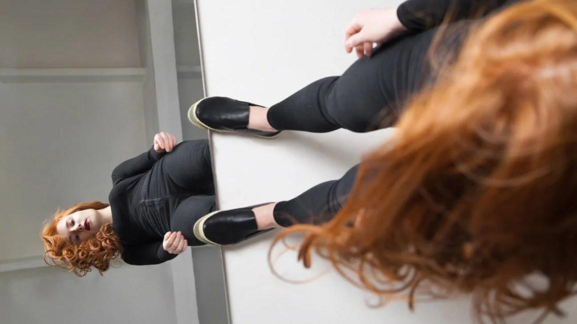 Una donna in piedi davanti a uno specchio controlla il suo riflesso.