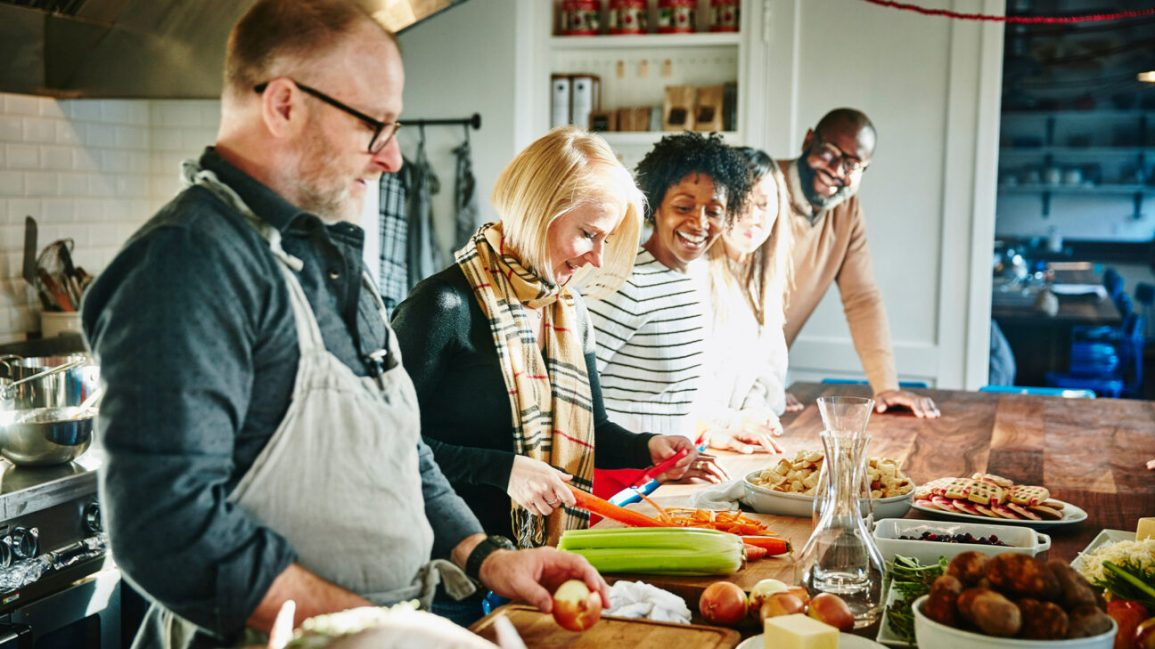Happy adults gather around table to prepare meal