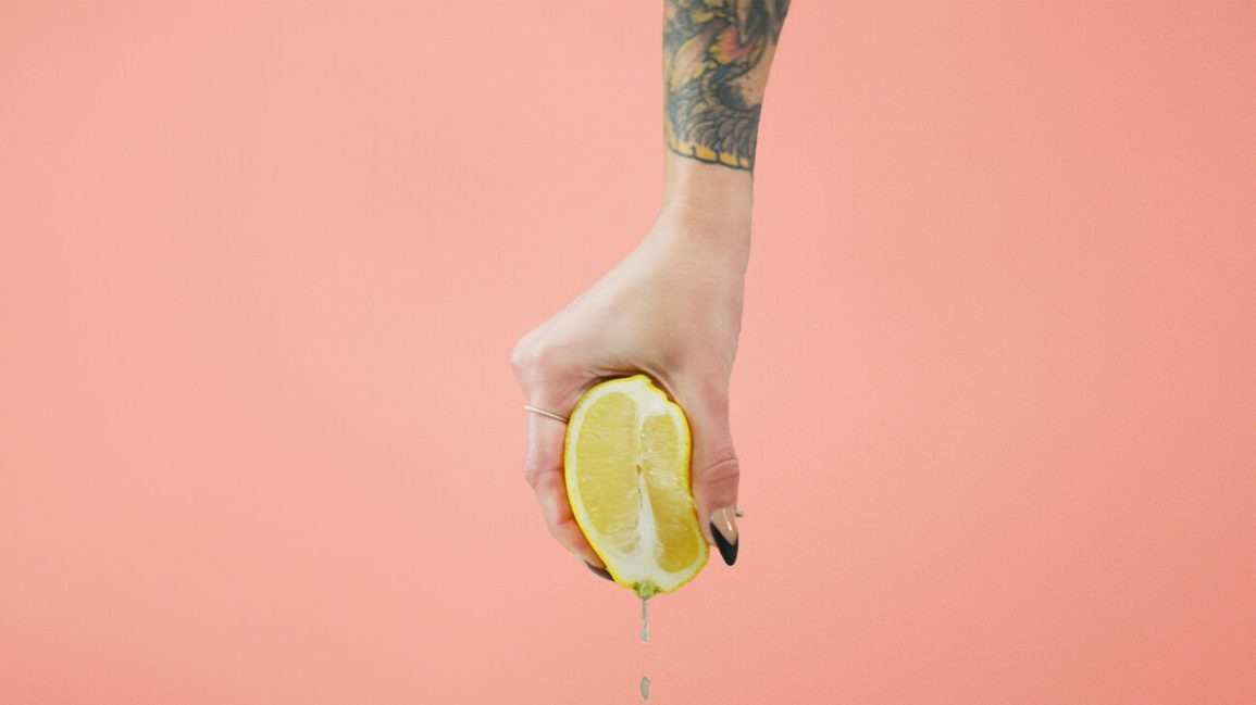 cropped image of a person with tattooed forearm and black stiletto acrylics holding a lemon half that's dripping juice