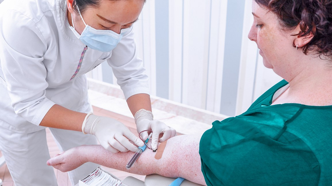 Medical professional draws blood from arm of patient