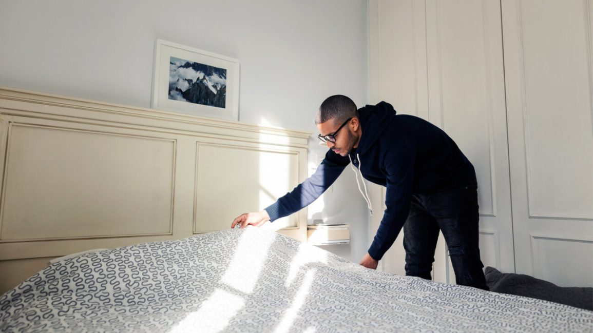 man making a bed with fresh sheets